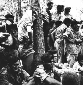 Eine Gruppe von Kämpfern der Jiftach-Brigade bei einer Kampfpause im Juli 1948. Bei dem Soldaten links unten ist die Nummer von Auschwitz zu sehen. - Quelle: Yad Vashem